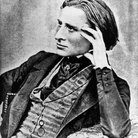 Fanz Liszt leaning graciously on a piano
